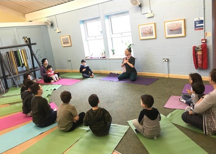 Children take part in a yoga workshop sat in a semi circle